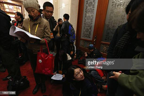 Media wait to be allowed access to the main hall the inside the Great Hall of the People during the closing session of the 18th National Congress of...