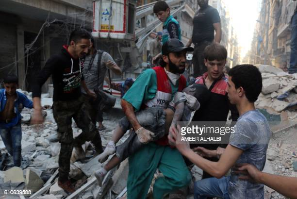 A medic carries the body of a boy after he was pulled from the rubble following a government forces air strike on the rebelheld alShaer neighbourhood...