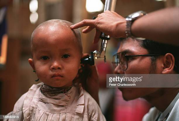 Medic checks a small child's ears at a clinic in a Karen refugee camp north of the Thai town, Mae Sot. Camps in this area are filled with Burmese...