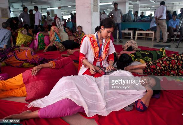 A medic checks on a garment worker who is participating in a hunger strike at a Tuba Group factory August 4 2014 in Dhaka Bangladesh Garment workers...