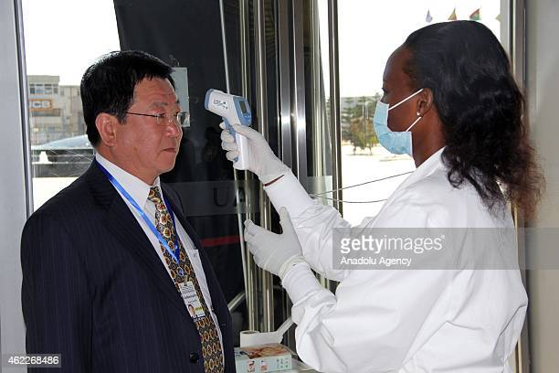 A medic checks the body temperature of an attendee for Ebola virus before the 26th Ordinary Session of African Union at the African Union...