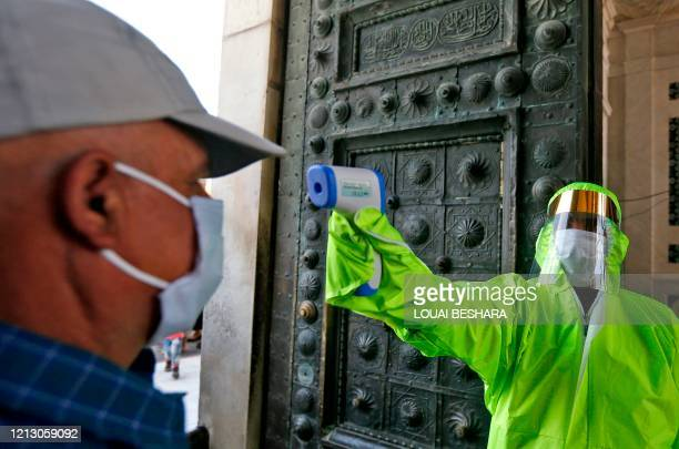 Medic checks the temperature of a Syrian worshipper before entering the Umayyad Mosque in Damascus to attend the Friday prayer on May 15 following...