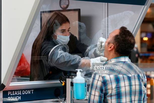 Medic collects a swab sample from a traveller at a booth at the COVID-19 coronavirus rapid testing centre in Israel's Ben Gurion International...