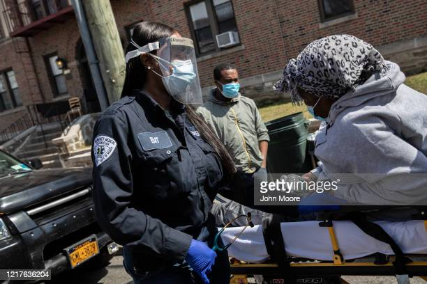 A medic from Empress EMS receives a suspected COVID19 patient from a home for transport to a hospital on April 07 2020 in Mount Vernon New York...