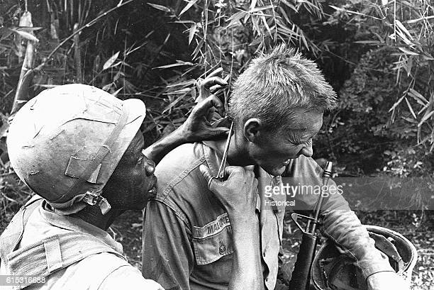 A medic from the 1st Cavalry Division gives first aid to a slightly wounded soldier who winces in pain Vietnam October 28 1965