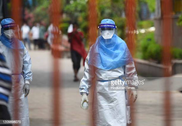 Medic in a Personal Protective Equipment kit during the cremation of a Covid-19 victim, at Nigambodh Ghat on April 14, 2020 in New Delhi, India....