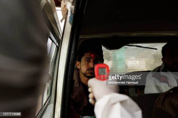 Medic in a protective suit checks the body temperature of people on their vehicles at a street as preventive measures amid fears from the spread of...