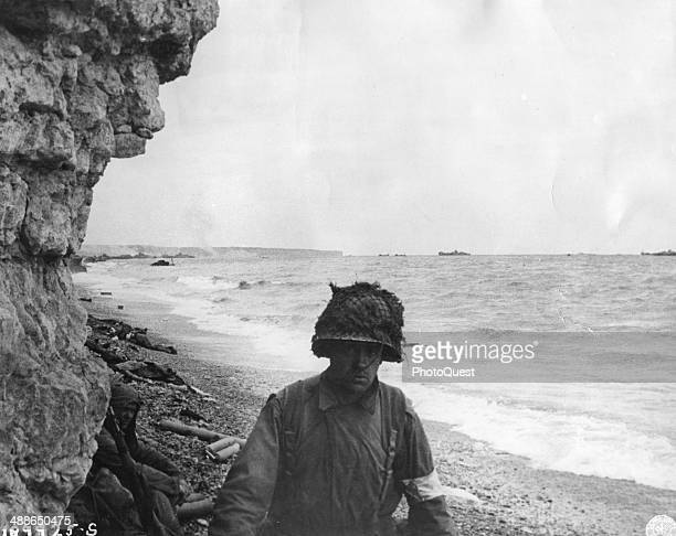A medic of the 3rd Battalion 16th Infantry Regiment 1st US Infantry Division moves along a narrow strip on Omaha Beach administering first aid to men...