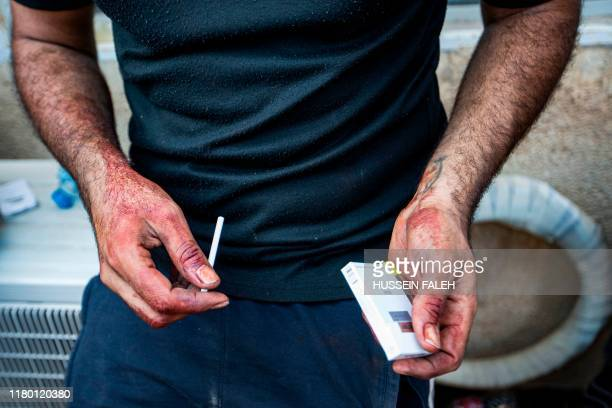 A medic prepares to smoke a cigarette during a break after attending to Iraqi protesters at a demonstration outside the southern port of Umm Qasr on...