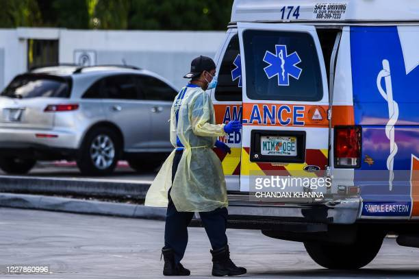 Medic prepares to transfer a patient on a stretcher from an ambulance outside of Emergency at Coral Gables Hospital where Coronavirus patients are...