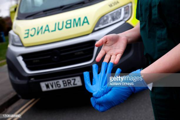 Medic removes nitrile gloves after working with an elderly patient in Hartley Wintney on March 28, 2020. - The two men leading Britain's fight...