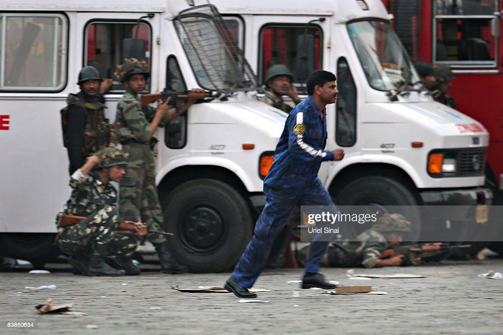 A medic runs for cover as Indian soldiers take up position outside the Taj Mahal Palace & Tower Hotel hotel during an armed siege, on November 28, 2008 in Mumbai, India. The city of Mumbai was rocked by multiple coordinated terrorist attacks that targeted locations popular with foreigners, late on the night of November 26 and into the next morning, killing scores and wounding hundreds in shootings and blasts around the city