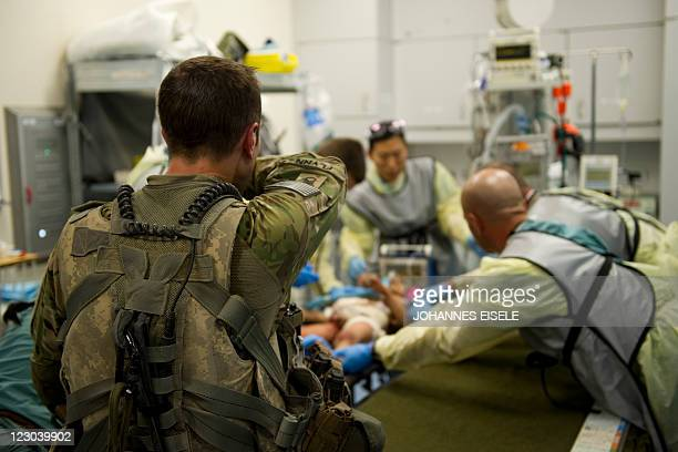 US Medic Stephan Flynn reacts as a wounded Afghan child shot in the stomach by suspected militants receives treatment at the Kandahar hospital Role 3...