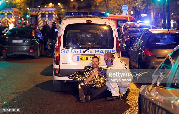 A medic tends to a man November 13 2013 in Paris France Gunfire and explosions in multiple locations erupted in the French capital with early...