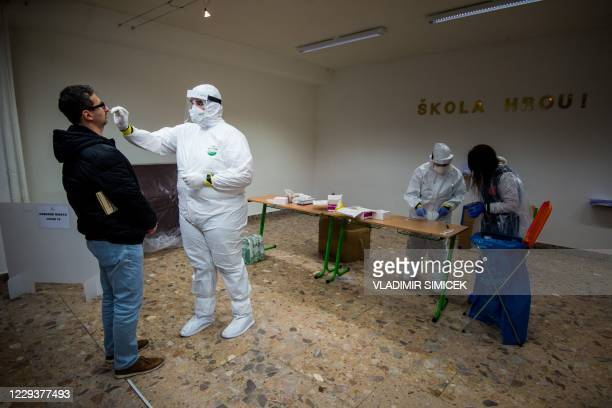 Medic tests a man for the novel coronavirus COVID-19 during nationwide testing in Bratislava, Slovakia on October 31, 2020. - Slovakia on october 31,...