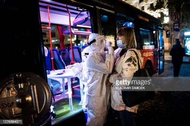 Medic tests a woman for the novel coronavirus COVID-19 during nationwide testing in Bratislava, Slovakia on October 31, 2020. - Slovakia on October...