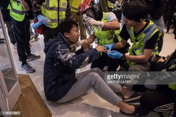 Medic treats a man who was hit by pepper spray deployed by police after a pro-democracy protest inside a shopping mall in Sheung Shui in Hong Kong on...