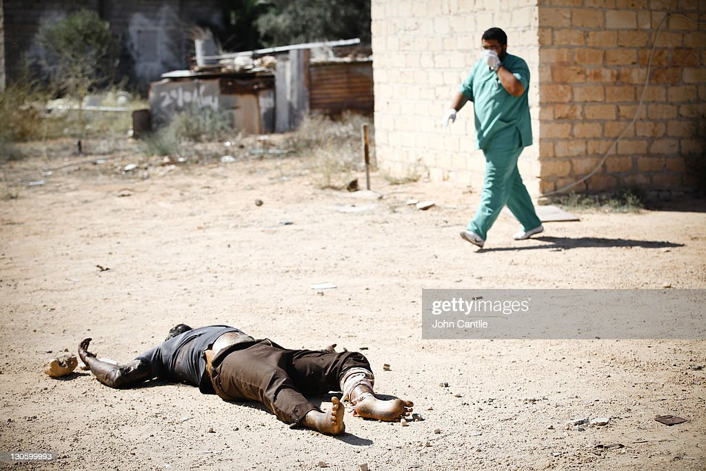 A medic walks past the week-old corpse of a prisoner executed after Mutassim Gaddafi's order in Colonel Gaddafi's home city of Sirte on October 14, 2011 in Libya. NTC forces are continuing their advance on Colonel Muammar Gaddafi's hometown of Sirte.