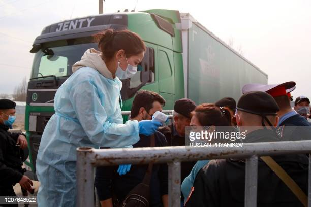 A medic wearing a protective gear checks the temperature of a woman at a checkpoint on the outskirts of Almaty on March 19 after authorities locked...