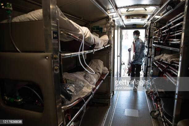 Medic wearing personal protective equipment prepares to unload COVID-19 patients arriving to the Montefiore Medical Center Moses Campus on April 07,...
