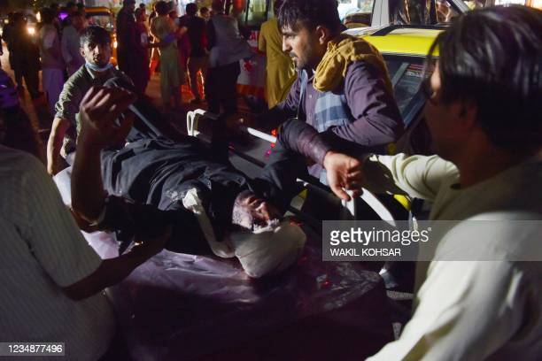 Medical and hospital staff bring an injured man on a stretcher for treatment after two blasts, which killed at least five and wounded a dozen,...
