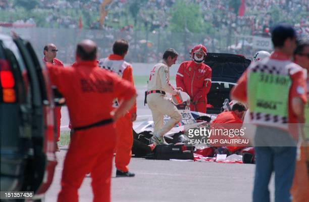 Medical and security personnel surround the crashed car of Ayrton Senna at the Imola track 01 May 1994 Senna died after crashing in the seventh lap...
