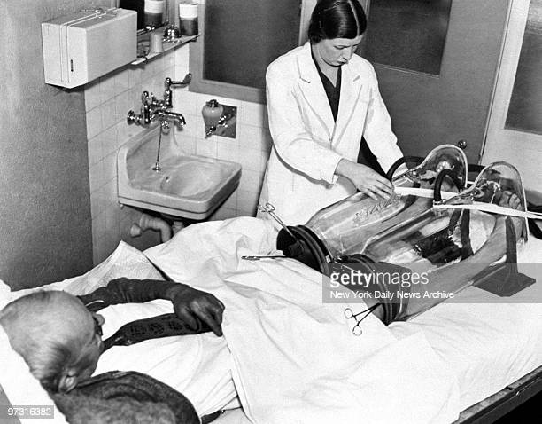 Medical apparatus at New York Hospital used in disturbances of circulation in extremities to prevent gangrene is being used to treat the feet of...