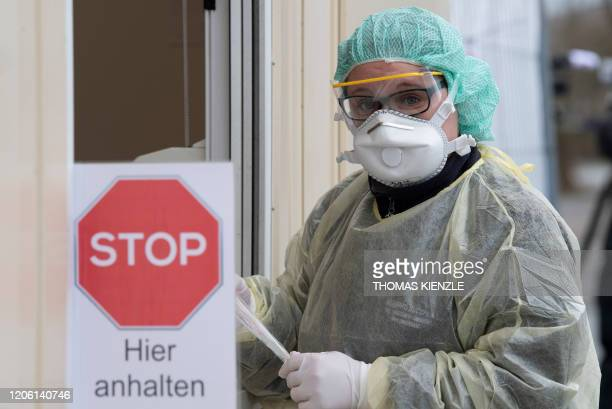 """Medical assistant holds a test kit for the novel coronavirus SARS-CoV-2, which can cause COVID-19, at the new """"Drive-In"""" in Nuertingen, southern..."""