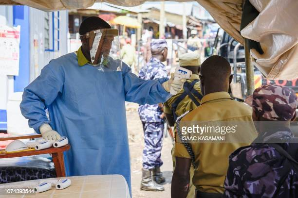 A medical assistant uses a noncontact thermometer to check the temperature of people from Democratic Republic of Congo at the Ebola screening point...