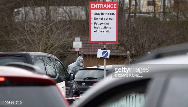"""Medical assistant wearing protective clothing talks to car drivers lining up at the entrance to the new """"Drive-In"""" for tests of the novel coronavirus..."""