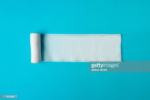 medical bandage untwisted on a blue background. health concept. healthy lifestyle concept. the concept of pharmacology. the concept of medicines. the concept of medical instruments. medicine concept. - bandage stock pictures, royalty-free photos & images