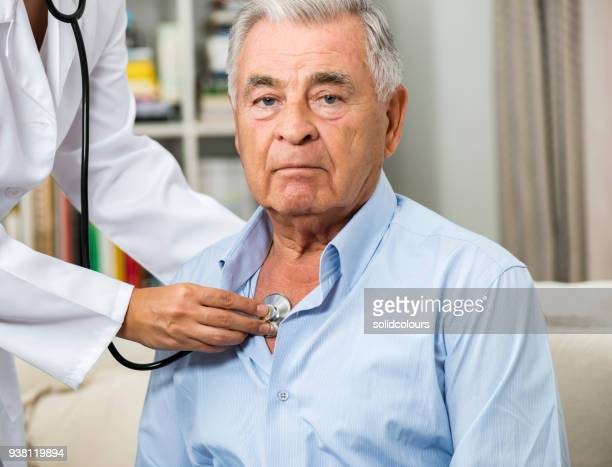 medical caring for senior man at home - heart attack stock photos and pictures