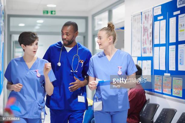 medical clinic team walking - group of doctors stock pictures, royalty-free photos & images