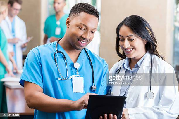 Medical colleagues look at something on a digital tablet