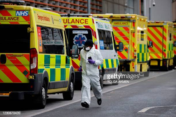 Medical delivery driver wearing PPE runs along a line of parked ambulances outside the Royal London hospital in London on January 19, 2021. - An...