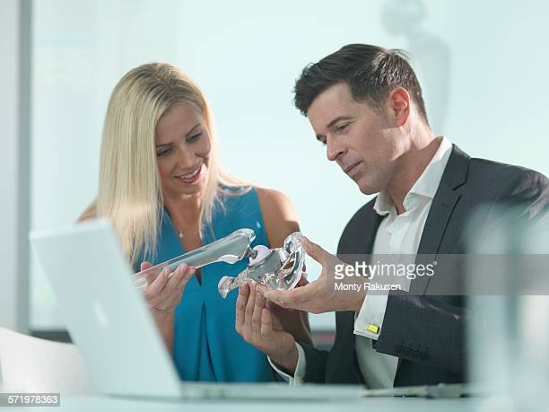 Medical designers inspecting hip joint model