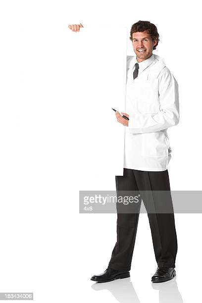 Medical doctor pointing with pen at blank poster board