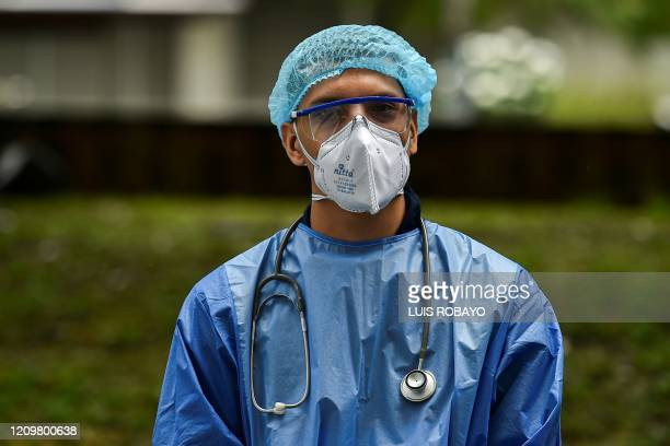 A medical doctor prepares to check Venezuelan migrants to rule out the novel coronavirus as part of their repatriation process in Cali Colombia on...