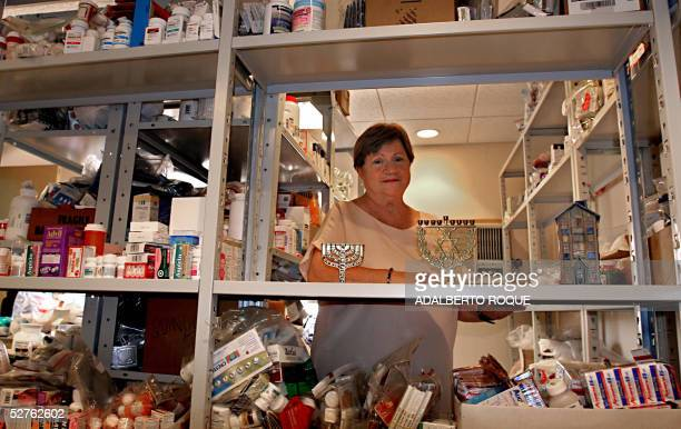 Medical doctor Rosa Behar a Cuban Jew poses 04 May 2005 at her flat in Havana with religious objects and medicines from international Jewish...