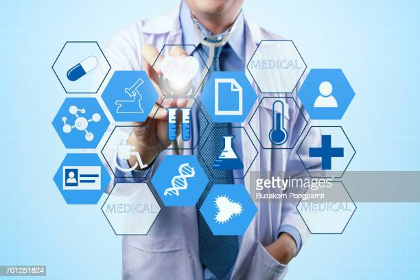 medical doctor touching virtual interface button of healthcare application - people icons stock pictures, royalty-free photos & images
