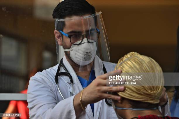 A medical doctor wears a face mask and shield as he examines a patient with symptoms of the new coronavirus in Tegucigalpa on April 6 2020 The...