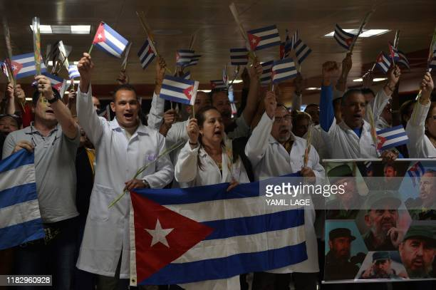 Medical doctors wait with Cuban national flags and portraits of Cuban late leader Fidel Castro for fellowmen returning from Bolivia at the Jose Marti...
