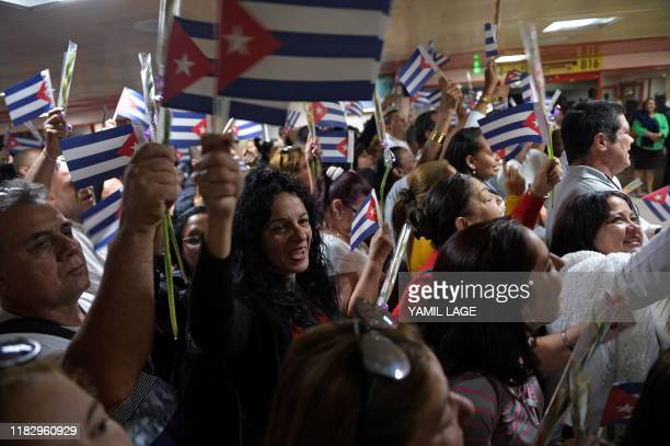 Medical doctors wait with Cuban national flags for fellowmen returning from Bolivia at the Jose Marti International airport in Havana on November 16...