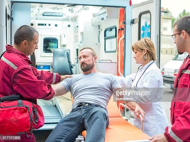 medical emergency team helping injured man - medical symbol stock pictures, royalty-free photos & images