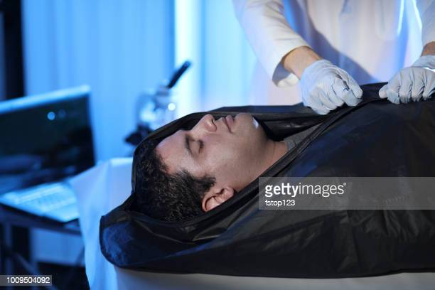 medical examiner with corpse in morgue. - body bag stock photos and pictures