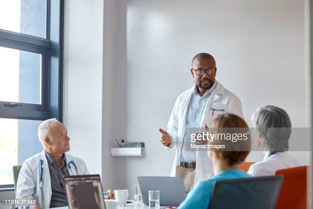 medical expert giving presentation during meeting - health care professional stock pictures, royalty-free photos & images