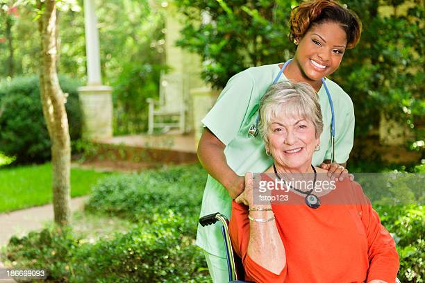 Medical:  Happy caregiver and patient outside a home.