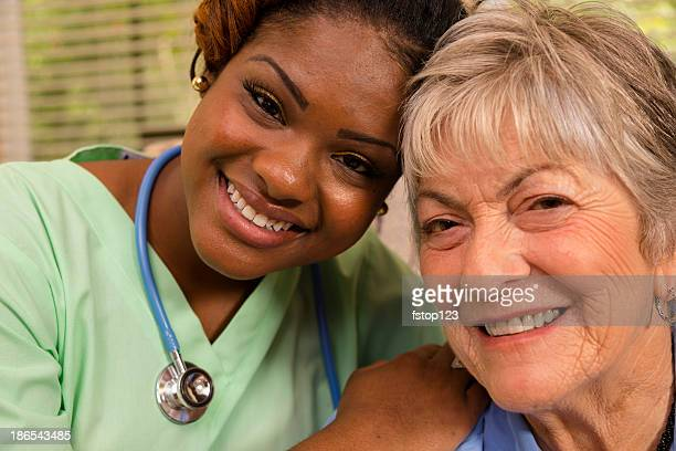 Medical: Happy senior woman gets hug from nurse. Assisted living.