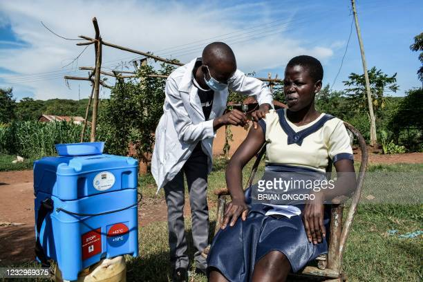 Medical health worker injects the Oxford/AstraZeneca Covid-19 vaccine to a woman as they visit door-to-door to deliver the vaccines to people who...