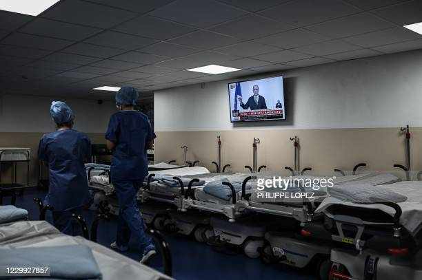 Medical health worker walk next to a television broadcasting French Prime Minister as he speaks during a press conference to outline France's...